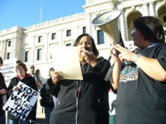 Woman speaking on bullhorn in front of MN State Capitol building.