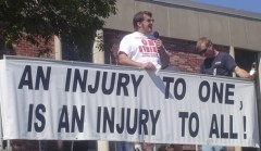 "Ludwig with banner: ""An injury to one is an injury to all."""
