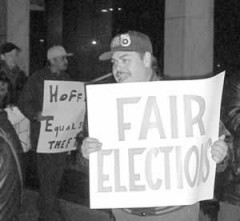 "Tony holding sign saying, ""Fair Elections."""