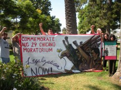 Activists raise a banner commemorating the August 29 Chicano Moratorium.