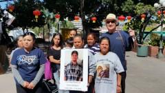 Estela Rodriguez holding poster of her son, Edwin Rodriguez