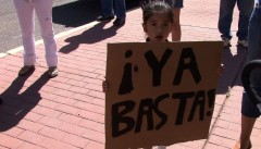 "Protester holding a sign that says ""Ya basta!"""