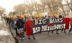 "Protesters march down 2nd Ave holding a banner that says ""Big Banks Make Bad Nei"