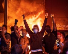 People celebrate as the Minneapolis Police Dept's Third Precinct burns