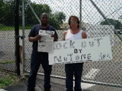 """Woman holding """"Locked out by NuTone"""" sign. Man holding Fight Back."""