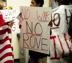 "Protester holding sign that says ""No War No Rove"""