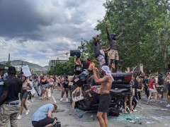 Protesters on top of a overturned police car in Salt Lake City.