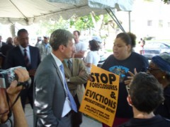 A protester holds a sign while talking to Minneapolis Mayor R.T. Rybak