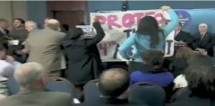 Protesters unfurl banner and confront anti-immigrant press conference.