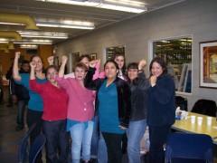 Women inside occupied factory raising fists