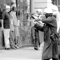 A photo of police aiming weapons at youth.
