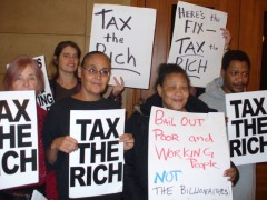 """Protesters holding signs that say """"Tax the Rich"""""""