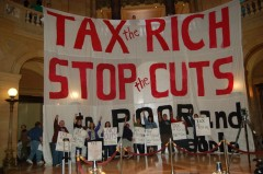 Members and supporters of Welfare Rights Committee stand in front of banner afte