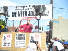 "Mick Kelly speaking at the podium, with a ""We need jobs now"" banner behind him"