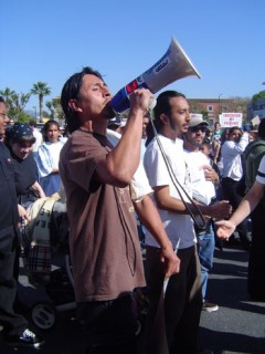 Man talking though bullhorn; palm trees in background