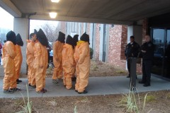 Immigrant rights activists in orange jumpsuit prisoner garb at ICE office in MN
