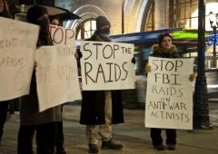 Protestors holding signs against FBI raids on antiwar movement
