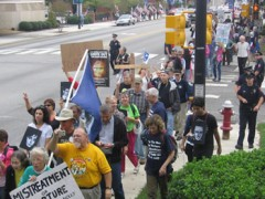 Protesters marching on sidewalk