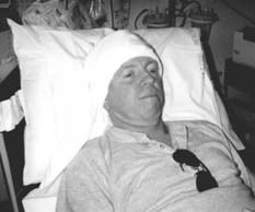Man with bandaged head in hospital bed.