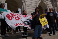 Protesters on steps of MN state capitol, with windblown banners, signs &amp; hair.