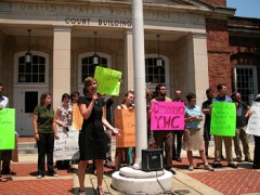 Photo of woman with microphone and protestors with signs in front of courthouse