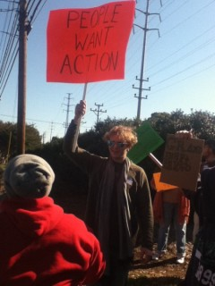 """Andrew Hobbs of Occupy Winston-Salem, holding a sign saying """"People Want Action"""""""