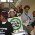 Marching up stairwell to UM presidents office.Sign:We're worth more.