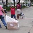 Woman dragging trash bag along sidewalk