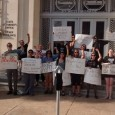 Protesters gather for a group photo outside of the State Attorney's office