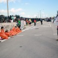 Protesters rally behind those wearing orange jumpsuits to block the entrance to