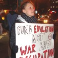 "Protestor holding sign that reads ""Fund Education Not War and Occupation"""