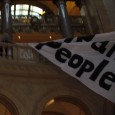 Cop tries, and fails, to pull down tax the rich banner inside Capitol.