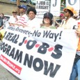 """People holding a banner that reads """"A a real jobs program now"""""""