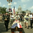 Veterans around and behind a flag-draped coffIn for USMC L/CPL ALEXANDER S. ARR