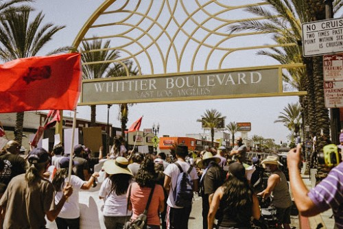 "Marchers passing under iconic ""Whittier Boulevard East Los Angeles"" landmark"