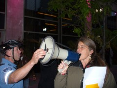 Cop tries to prevent Deb Konechne from leading chants at governor debate