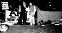 Two people giving a speech at night in front of banners