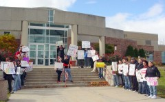 Students hold signs and protest against Rebecca Kleefish