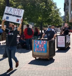 Stagehands pushing music road cases with signs reading Push for 600.