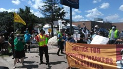 Protesters and banner that reads: Justice For Essential Workers at Strauss.
