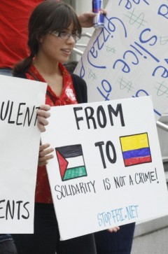 Sign with the Palestinian and Colombian flags at Tampa protest against FBI repre