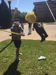 Student winding up to hit Trump piñata.