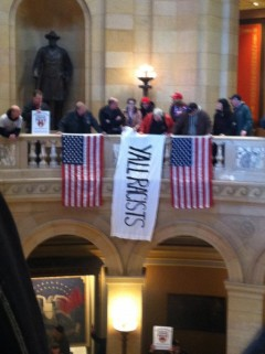 """Anti Trump protesters hold banner saying """"Y'all racists,"""" in MN Capitol."""