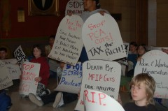 Protestors holding signs inside Governor Pawlenty's office