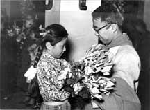 Girl handing man flowers