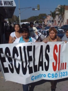 """Women carrying banner that says, """"Escuelas si... Centro CSO"""""""