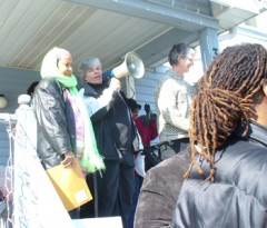 3 people on porch of a foreclosed home, with bullhorn