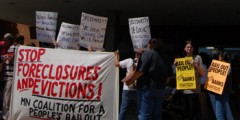 """Banner - """"Stop foreclosures and evictions."""" at protest"""