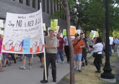 """March with picket signs and banners. """"Say no to the NED"""""""