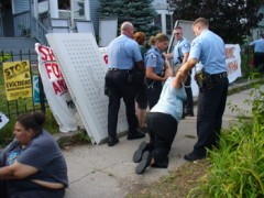 A protester is dragged away from the house by police